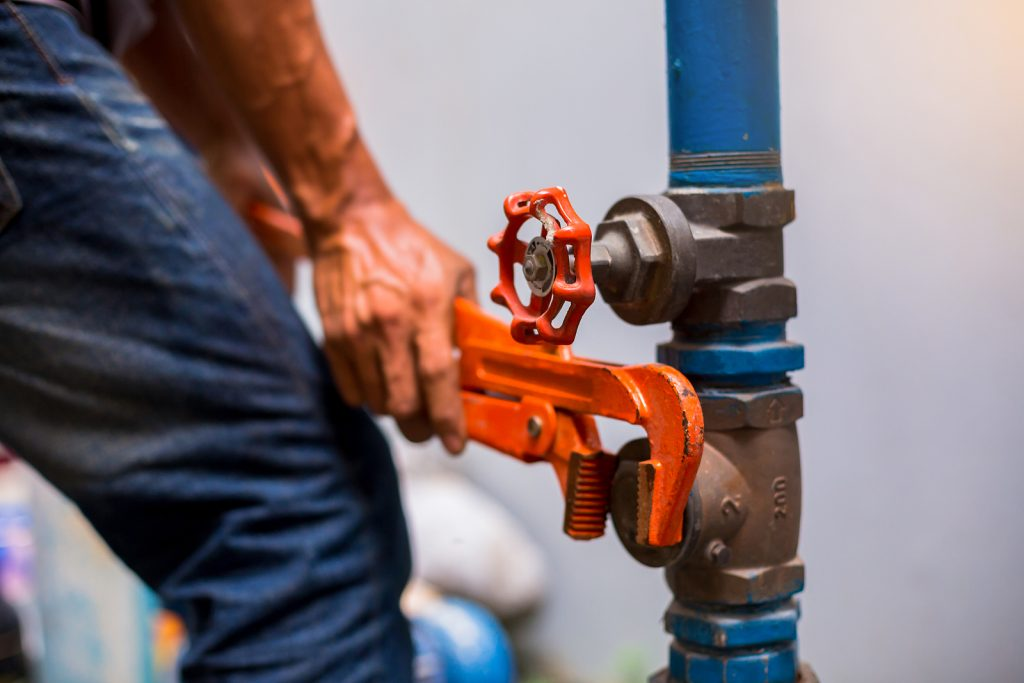 Plumber in Upper Hutt using a wrench to repair the water supply pipe